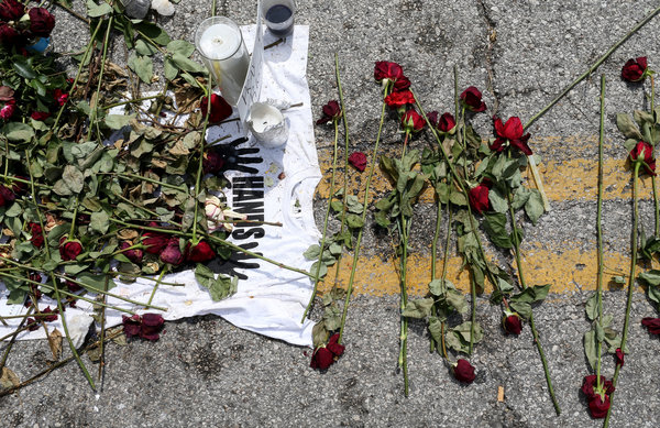 A makeshift memorial for Michael Brown on the spot on a Ferguson, Mo., street where his body lay for about four hours after he was shot by a police officer on Aug. 9. Credit Joe Raedle/Getty Images